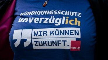 Postbankstreik: Postbank-Beschäftigte trägt ihre Forderung auf der Brust