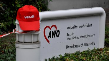 ver.di Mütze vor dem Schild der AWO