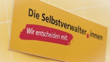 """ver.di-Veranstaltung zum Tag der Selbstverwaltung am 22.5.2018 in Berlin, Störer auf einem Aufsteller """"die Selbstverwalter*innen Wir entscheiden mit."""""""