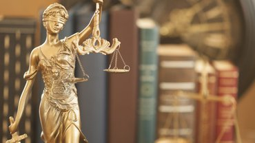 goldene Statuette der Justitia vor einem Bücherregal