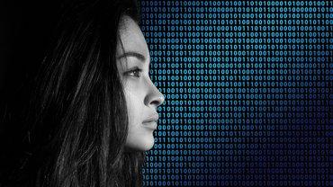 Das Gesicht einer Frau vor einer binären Code-Leinwand.
