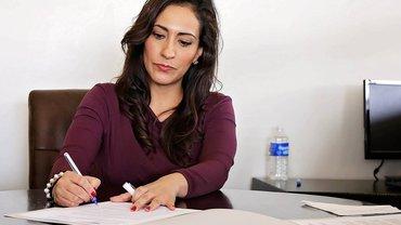 Eine Frau im Büro beim Ausfüllen von Dokumenten.